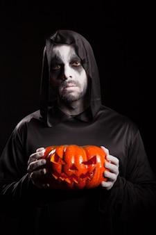 Gruseliger sensenmann, der einen kürbis über schwarzem hintergrund hält, halloween-outfit.