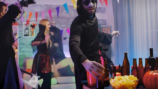Gruseliger sensenmann trinkt ein bier und feiert halloween mit seinen monsterfreunden, die tanzen und spaß haben
