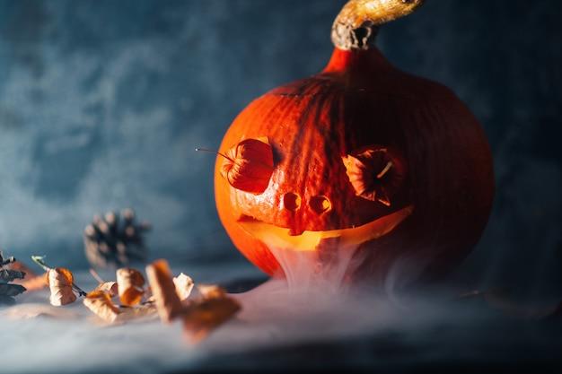 Gruseliger verrückter halloween-kürbis auf dunkler tabelle mit rauche