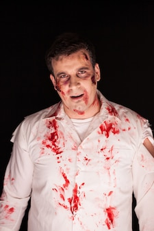 Gruseliger zombie mit blut auf ihm nach einem mord auf schwarzem hintergrund. halloween-outfit.