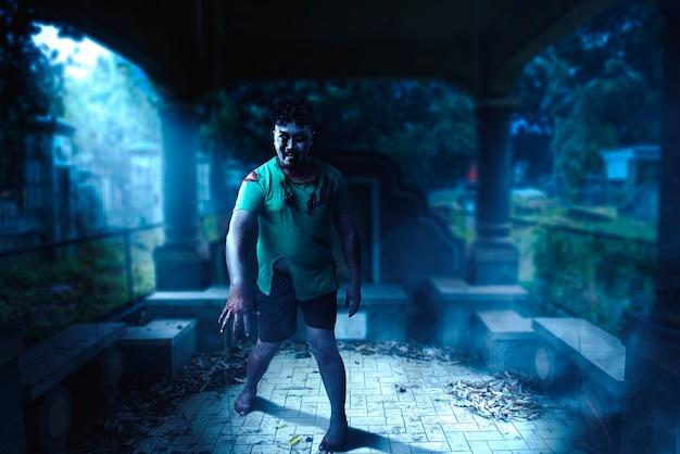 Gruseliger zombie mit blut und wunde am körper, der auf dem friedhof spaziert