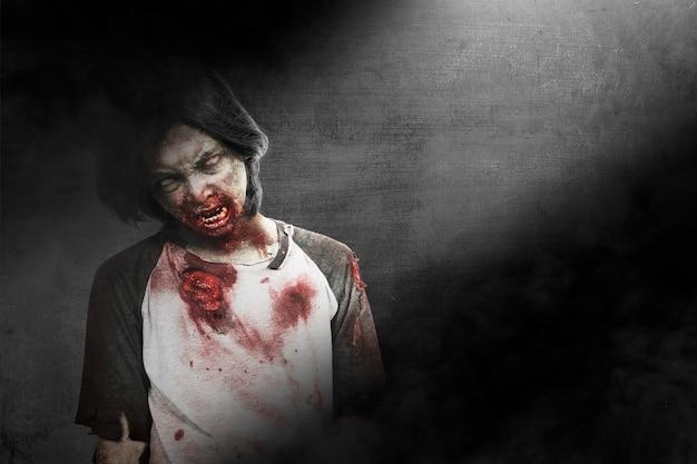 Gruseliger zombie mit blut und wunde an seinem körper, der mit dunklem hintergrund steht