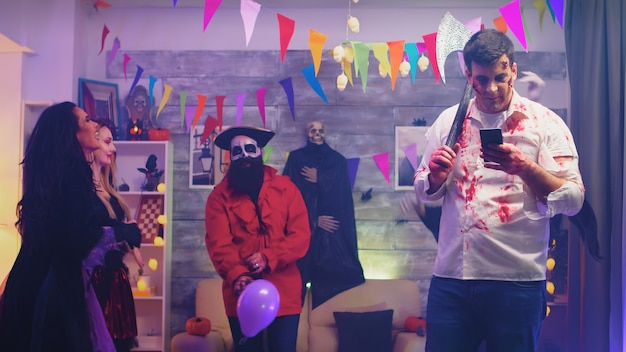 Gruseliger zombie mit einer axt, der sein telefon auf einer halloween-party mit anderen als monster verkleideten leuten benutzt.
