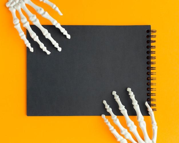 Gruseliges halloween-konzept der draufsicht mit den skeletthänden