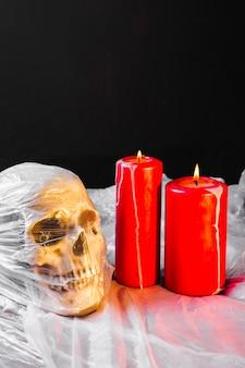 Gruseliges konzept mit roten kerzen und schädel