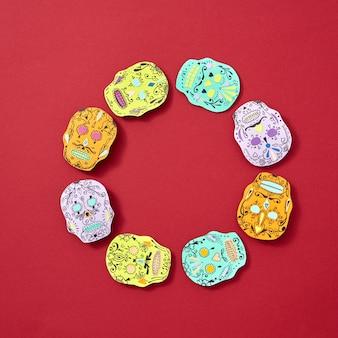 Gruseliges papier steht calaveras attributen des mexikanischen feiertags calaca in form eines runden rahmens auf einem roten hintergrund mit platz für text gegenüber. halloween-handwerkskarte. flach liegen