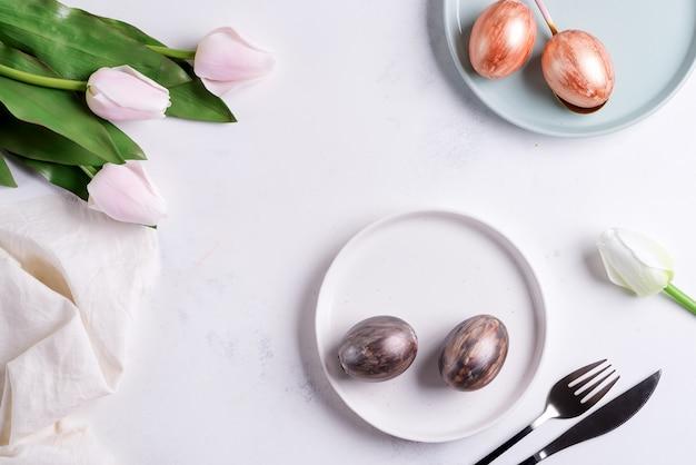 Gruß-osterkarte mit handgemachten hellen eiern auf tellern und tulpenblumen auf hellgrauem marmorhintergrund.
