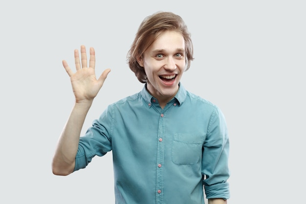 Gruß. porträt eines aufgeregten, gutaussehenden, langhaarigen, blonden jungen mannes im blauen hemd, der mit der hand winkt und in die kamera schaut und hallo sagt. indoor-studioaufnahme, isoliert auf hellgrauem hintergrund.