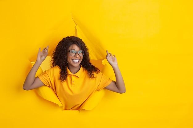Gruß stoppen fröhliche afroamerikanerin in zerrissenem blauem papierhintergrund