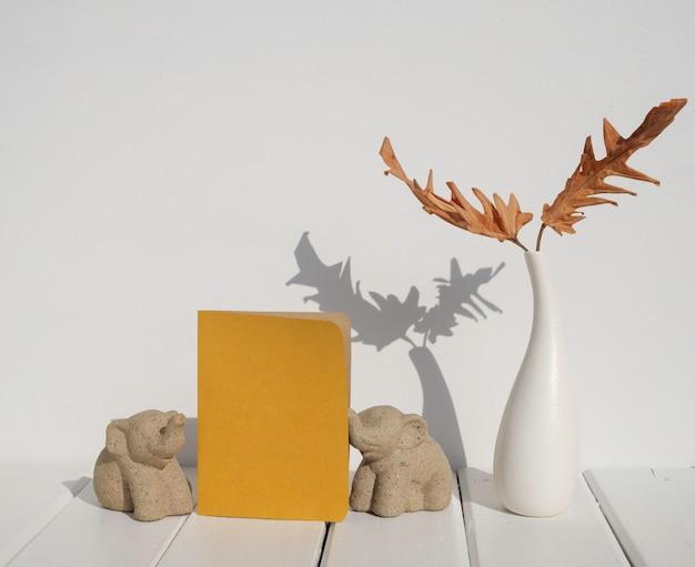Grußeinladungs-handwerkskartenmodell, getrocknetes blatt philodendron in der keramikvase, elefantenstatue auf weißer hölzerner tischrauminnenfläche mit langem schatten