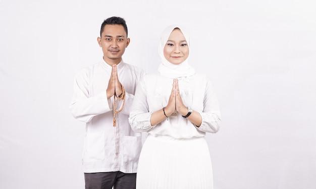 Grußgeste des asiatischen muslimischen paares auf ramadhan isoliert