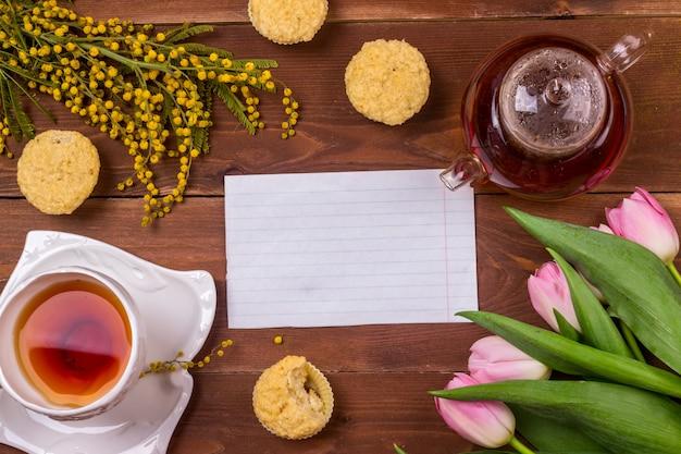 Grußkarte der frauen tagesmit tulpen, mimose, tee und kleinen kuchen auf braunem hölzernem hintergrund.