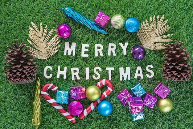 Grußkarte der frohen weihnachten mit dekoration auf grünem gras