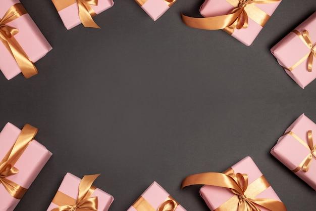 Grußkarte der frohen weihnachten und der frohen feiertage mit vielen überraschungsgeschenken mit goldatlasbändern auf dunklem hintergrund. flachgelegt, draufsicht