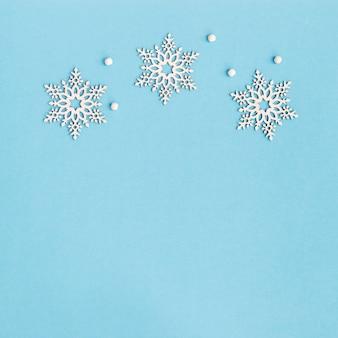 Grußkarte der frohen weihnachten und des guten rutsch ins neue jahr mit hölzernen schneeflocken auf blauem hintergrund