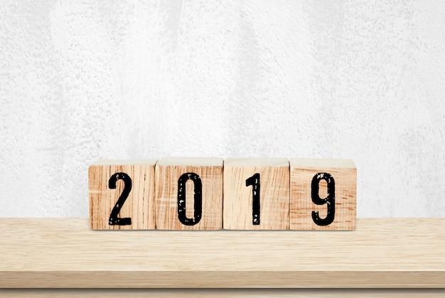 Grußkarte des neuen jahres 2019, hölzerne würfel mit 2019 auf hölzernem tabellenhintergrund