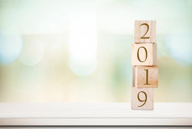Grußkarte des neuen jahres 2019, hölzerne würfel mit 2019 über unschärfe bokeh backgroud
