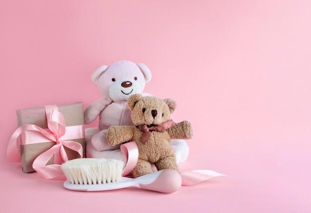 Grußkarte für babygeburt mit teddybären und babyhaarbürste auf rosa oberfläche bild mit kopienraum