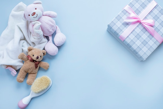 Grußkarte für babygeburt mit teddybärgeschenk und babyhaarbürste auf hellgrauer oberfläche bild mit kopienraum