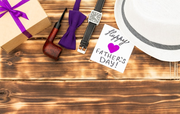 Grußkarte für den glücklichen vatertag mit einer geschenkbox und männeraccessoires auf einer rustikalen hölzernen tischplatte