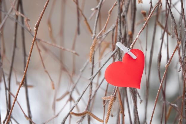 Grußkarte für valentinstagherzen in rosa. lächelnde herzen in liebe gucken hinter einer birke hervor.