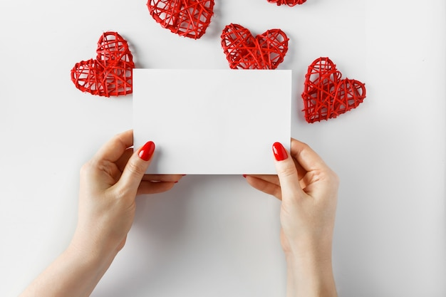 Grußkarte in den händen auf einem weiß zum valentinstag.