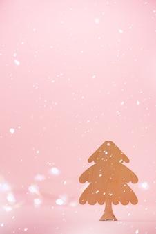 Grußkarte in minimalem stil. hölzerner weihnachtsbaum auf rosa hintergrund mit kopienraum, lichter bokeh, schnee.