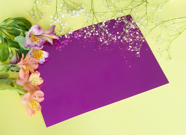 Grußkarte mit blumen. fahne mit alstroemeriablumen auf einem rosa hintergrund.