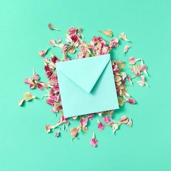 Grußkarte mit handgemachtem umschlag auf blütenblättern auf türkisfarbenem hintergrund und kopienraum. flach liegen. attrappe, lehrmodell, simulation.