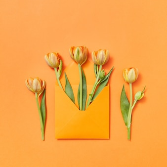 Grußkarte mit handwerksumschlag der gelben tulpen auf einem orange hintergrund. liebesbrief als geschenk. draufsicht.