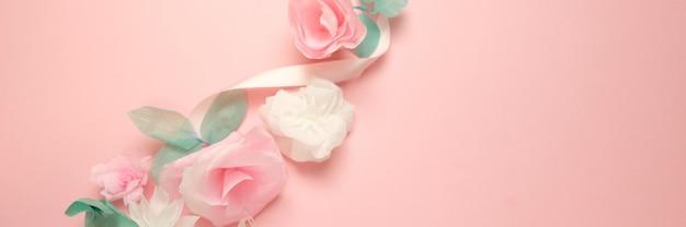 Grußkarte mit rosafarbenem fahnenhintergrund der papierblumen.