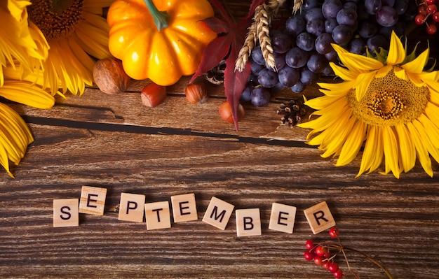 Grußkarte mit septembertext. zusammensetzung mit kürbis, herbstlaub, sonnenblume und beeren auf dem holztisch. gemütliches herbststimmungskonzept