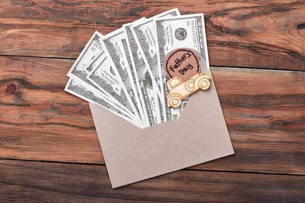 Grußkarte und dollar. umschlag und brandmalerei-auto. das nützlichste geschenk.