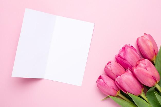 Grußkarte und rosa blumentulpen auf einer rosa oberfläche