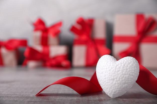 Grußkarte valentinstag mit herzen auf hölzernem und geschenkhintergrund. mit platz für ihre textgrüße