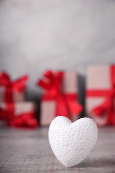 Grußkarte valentinstag mit herzen auf holz und geschenkhintergrund. mit weltraumgrüßen