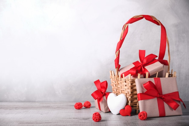 Grußkarte valentinstag mit herzen und geschenken im korb auf hölzernem hintergrund. mit platz für ihre textgrüße