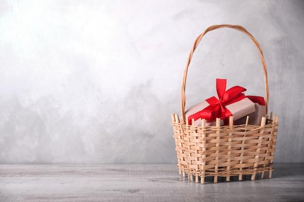 Grußkarte valentinstag oder neues jahr mit geschenken im korb auf hölzernem hintergrund. mit platz für ihre textgrüße