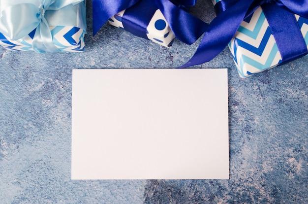 Grußkarte zum vatertag oder geburtstag. geschenkbox mit leerem weißem papier auf blauem hintergrund.