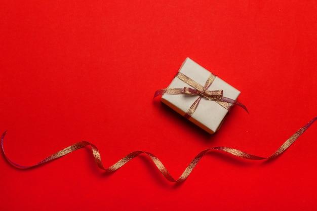 Grußkartenschablone mit schöner roter geschenkbox, bänder auf rotem hintergrund