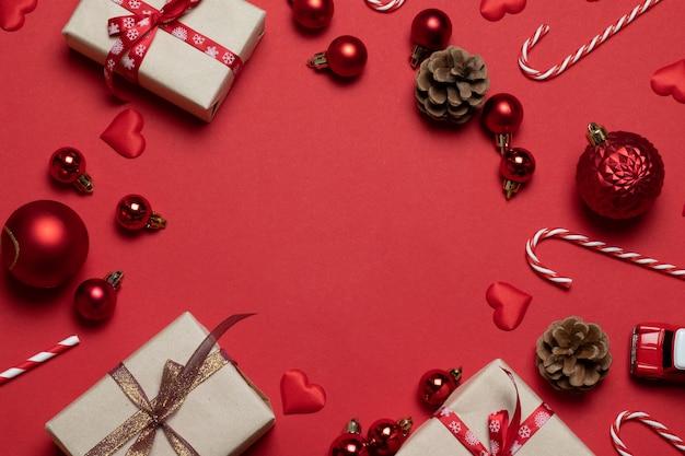 Grußrahmen der frohen weihnachten und des guten rutsch ins neue jahr mit kraftpapiergeschenkboxen, bandbogen, weihnachtskegeln, roten bällen und zuckerstangen.