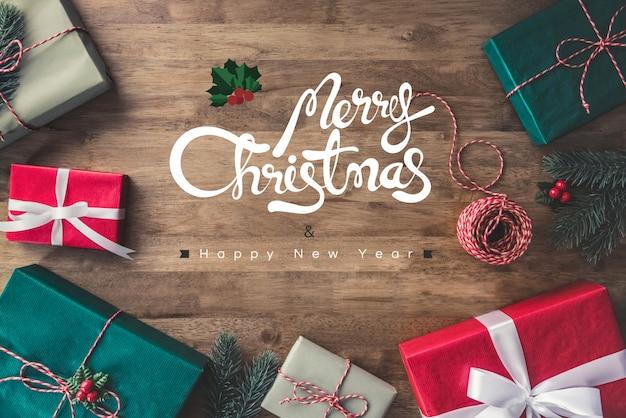 Grußtext der frohen weihnachten und des guten rutsch ins neue jahr auf einem holztischhintergrund mit geschenkboxen