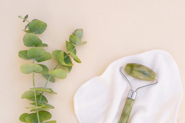 Gua sha, gesichtsmassage grüner jaderoller aus naturstein mit natürlichem eukalyptus