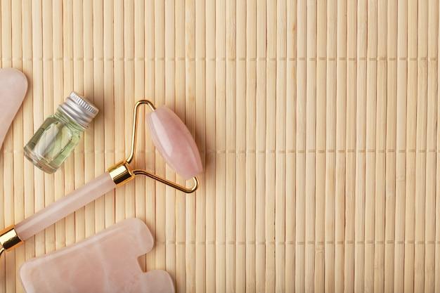 Gua sha massage aus natürlichem rosenquarz-roller, jadestein und öl auf bambushintergrund für gesichts- und körperpflege.