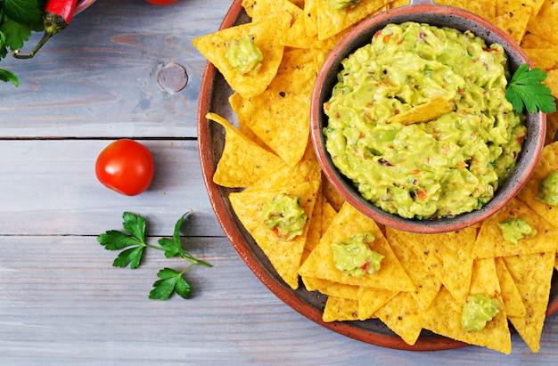 Guacamole avocado, limette, tomate, zwiebel und koriander, serviert mit nachos - traditioneller mexikanischer snack. flach liegen. .