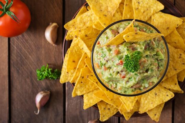 Guacamole avocado, limette, tomate, zwiebel und koriander, serviert mit nachos - traditioneller mexikanischer snack