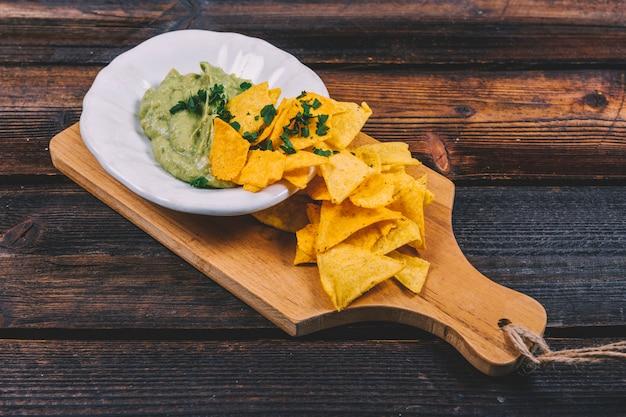 Guacamole in der schüssel mit mexikanischen nachos auf hölzernem schneidebrett