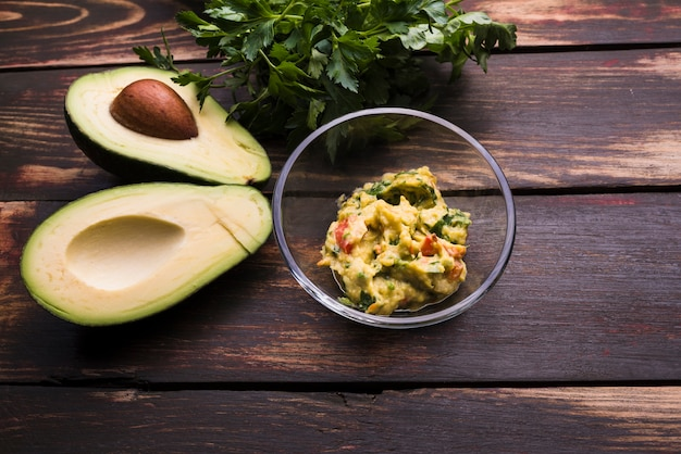 Guacamole in schüssel und avocados in der nähe von kräutern