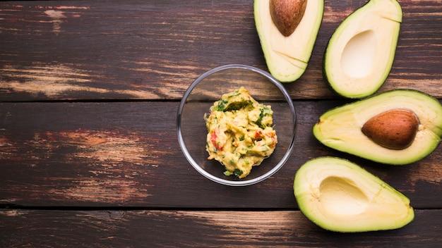 Guacamole in schüssel und avocados