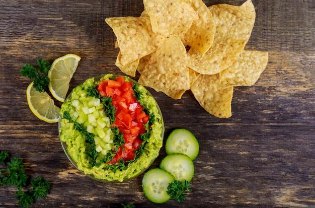 Guacamole mit corn chipe auf rustikalem holztisch